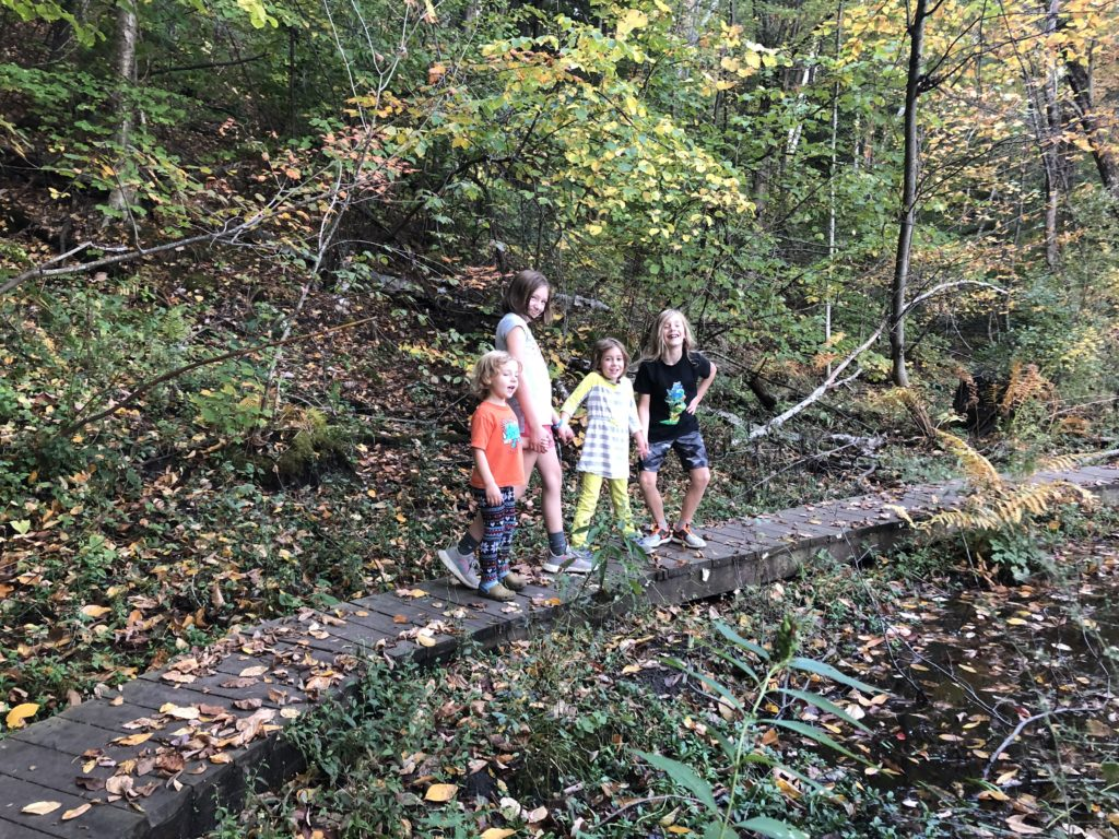 Forrester kids pose on a raised wooden path on one section of trail.