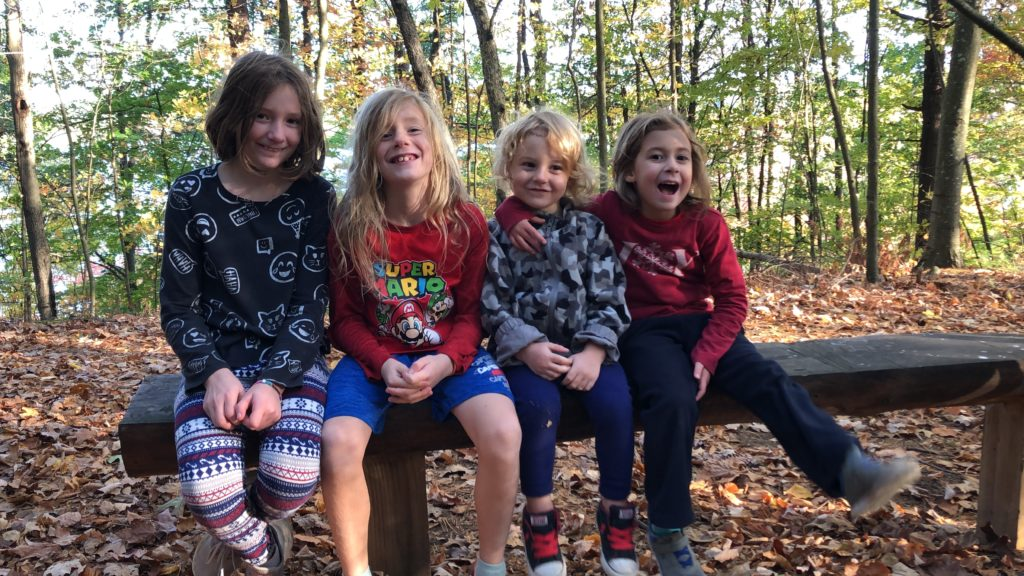 Rayleigh, Dillon, Grayson, and Ainsley resting on a bench at the top of a hill.