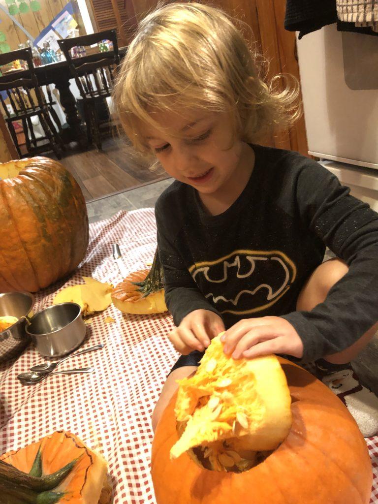 Grayson looking unsure as he gingerly lifts his pumpkin lid, revealing the pumpkin guts inside.