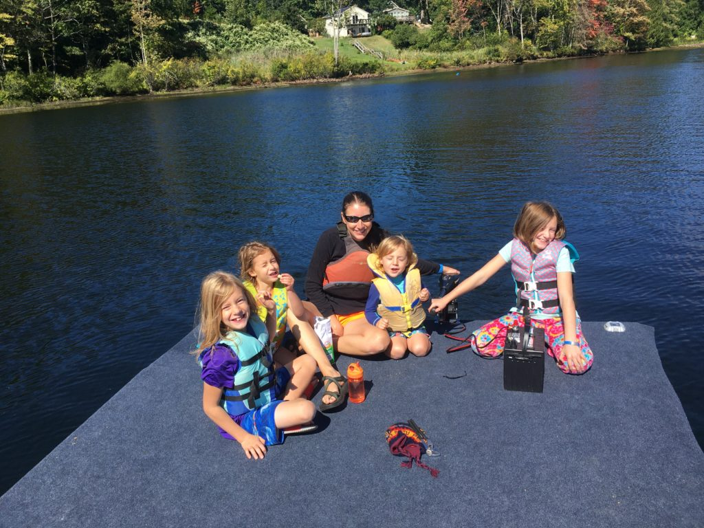Kelsey and the kids eating snacks on the floating dock while Rayleigh steers the motor.