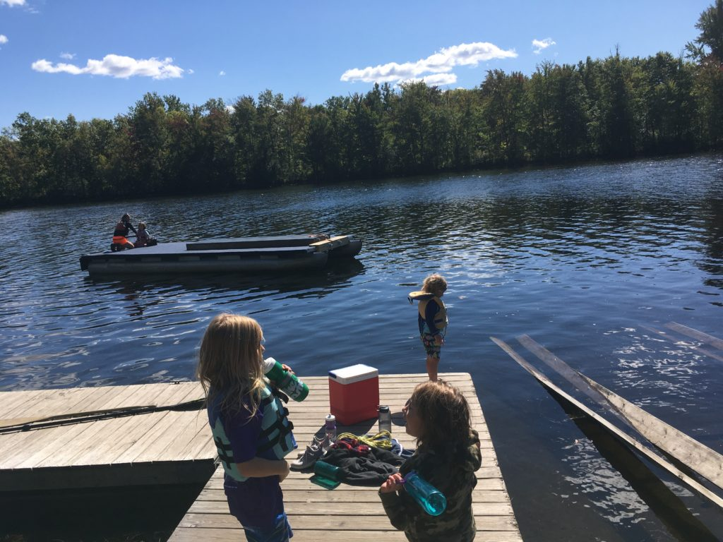 Kelsey and Rayleigh navigating the floating dock toward the trailer at the boat launch while the other kids look on from shore.
