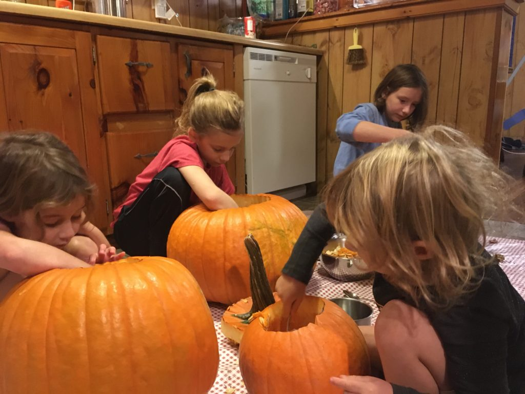 Ainsley, Dillon, Grayson, and Rayleigh scooping out their pumpkins on a vinyl tablecloth on the kitchen floor.