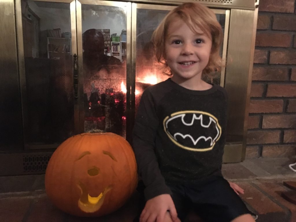Grayson sitting in front of the fireplace with his pumpkin, which is carved to look like it has a clown's face.