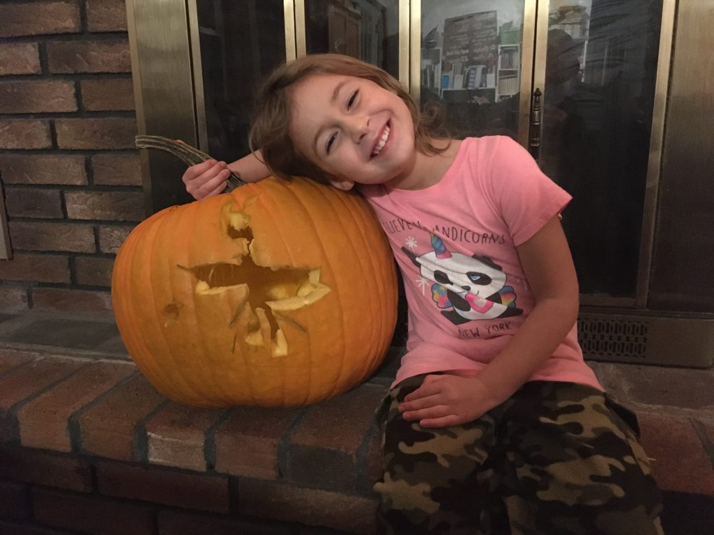Ainsley sitting in front of the fireplace with her pumpkin.