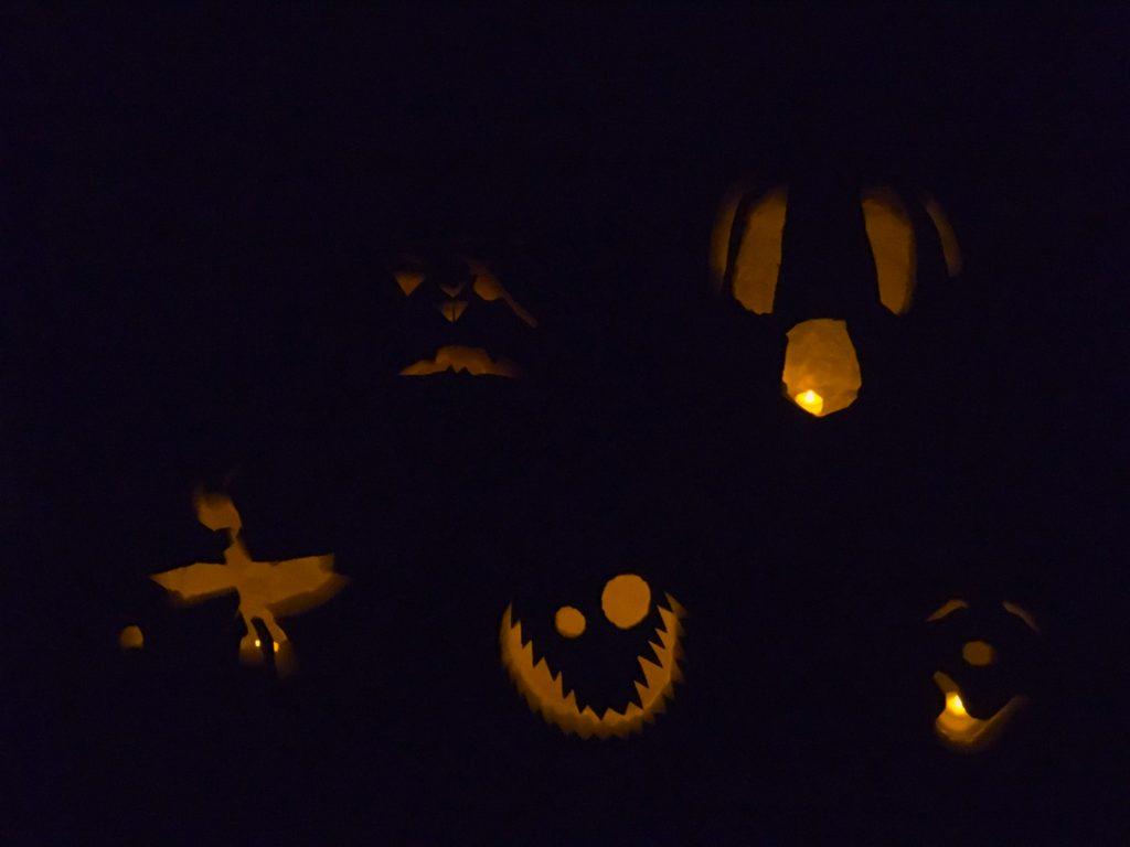 Five lit-up jack-o-lanterns in the dark.