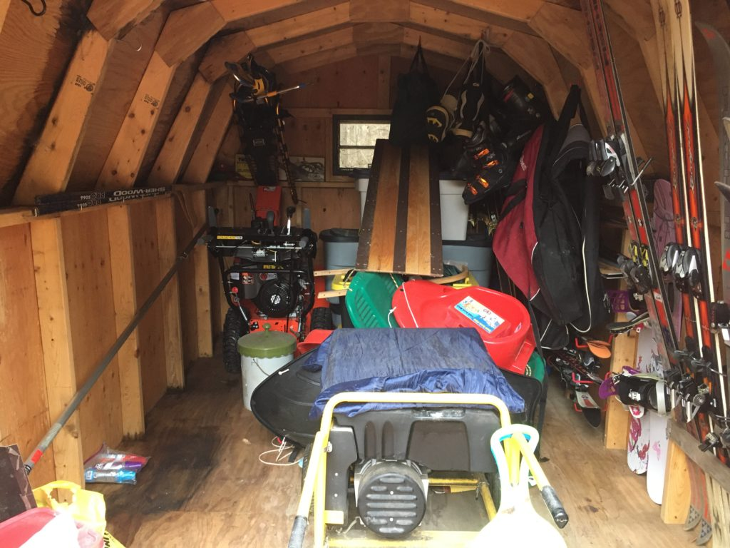 A photograph of the inside of our storage shed containing our winter gear, including skis, snowboards, the snowblower, a generator, sleds, and several tubs.
