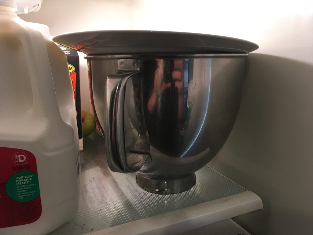 A photo of the Kitchen Aid metal mixer bowl, full of liquid ice cream, set in the refrigerator to chill.