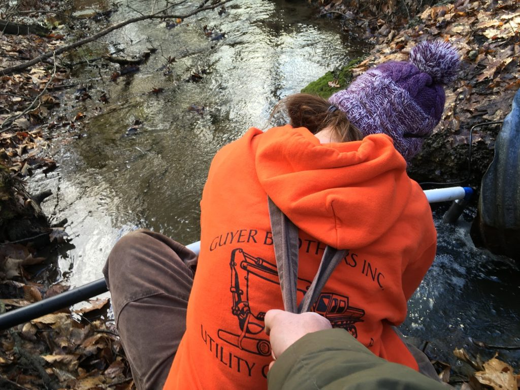 A photo of Kevin holding Kelsey above the stream by her overall straps while she installs the sump pump.