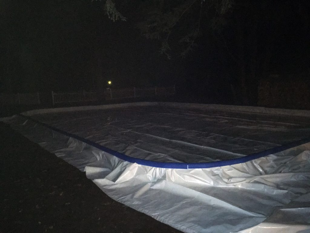 A photo of the finished rink, with liner and foam edge protectors installed, at night.