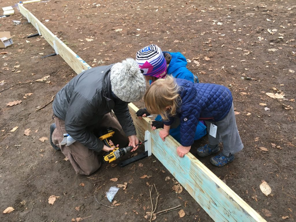 A photo of Kelsey screwing in a support stake to the rink wall while Rayleigh and Grayson help support the boards.