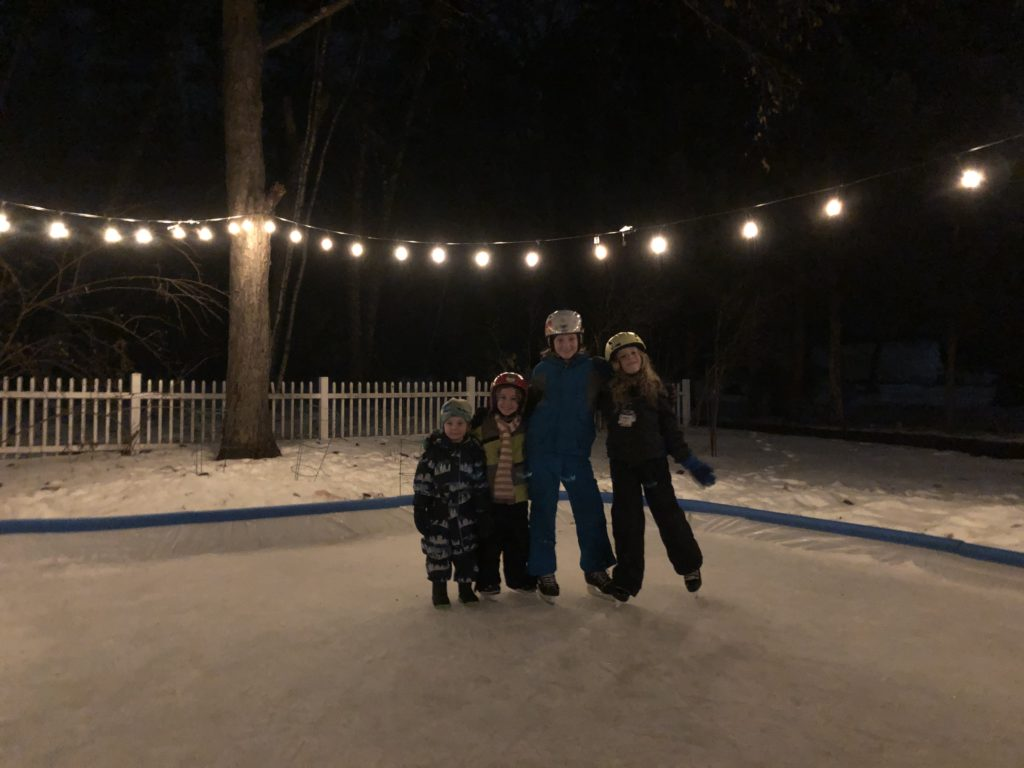 A photo of Grayson, Ainsley, Rayleigh, and Dillon skating at night with patio lights overhead.
