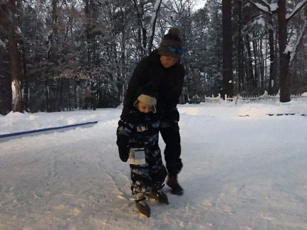 A photo of Kelsey teaching Grayson how to skate.